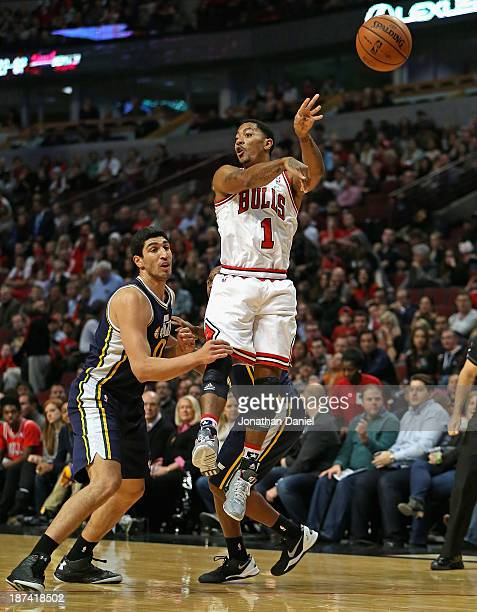 Derrick Rose of the Chicago Bulls leaps to pass over Enes Kanter of the Utah Jazz at the United Center on November 8 2013 in Chicago Illinois NOTE TO...