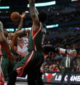 Derrick Rose of the Chicago Bulls looses control of the ball between Brandon Knight and Larry Sanders of the Milwuakee Bucks during a preseason game...