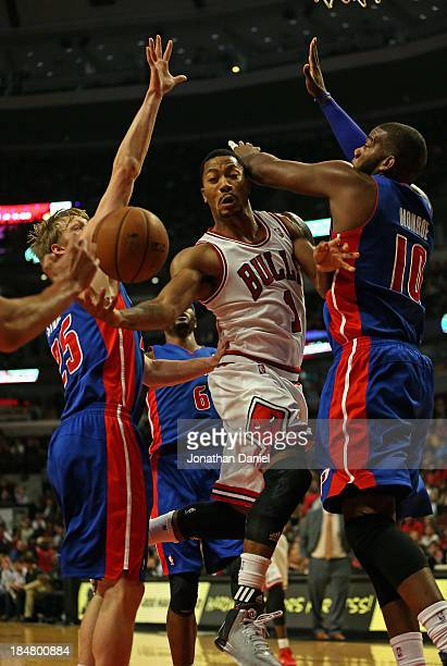 Derrick Rose of the Chicago Bulls passes between Kyle Singler and Greg Monroe of the Detroit Pistons during a preseason game at the United Center on...