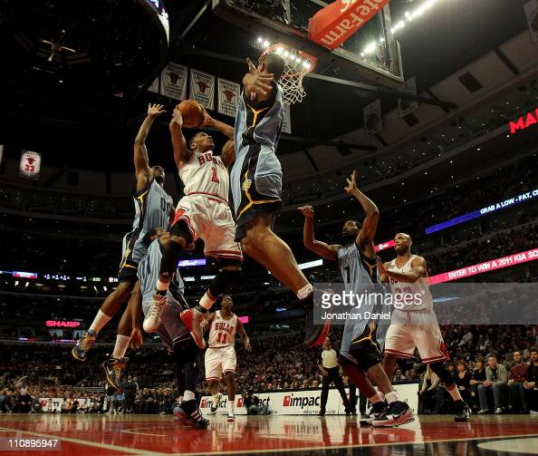 Derrick Rose of the Chicago Bulls puts up a shot between Darrell Arthur Mike Conley and Shane Battier of the Memphis Girzzlies on his way to a...