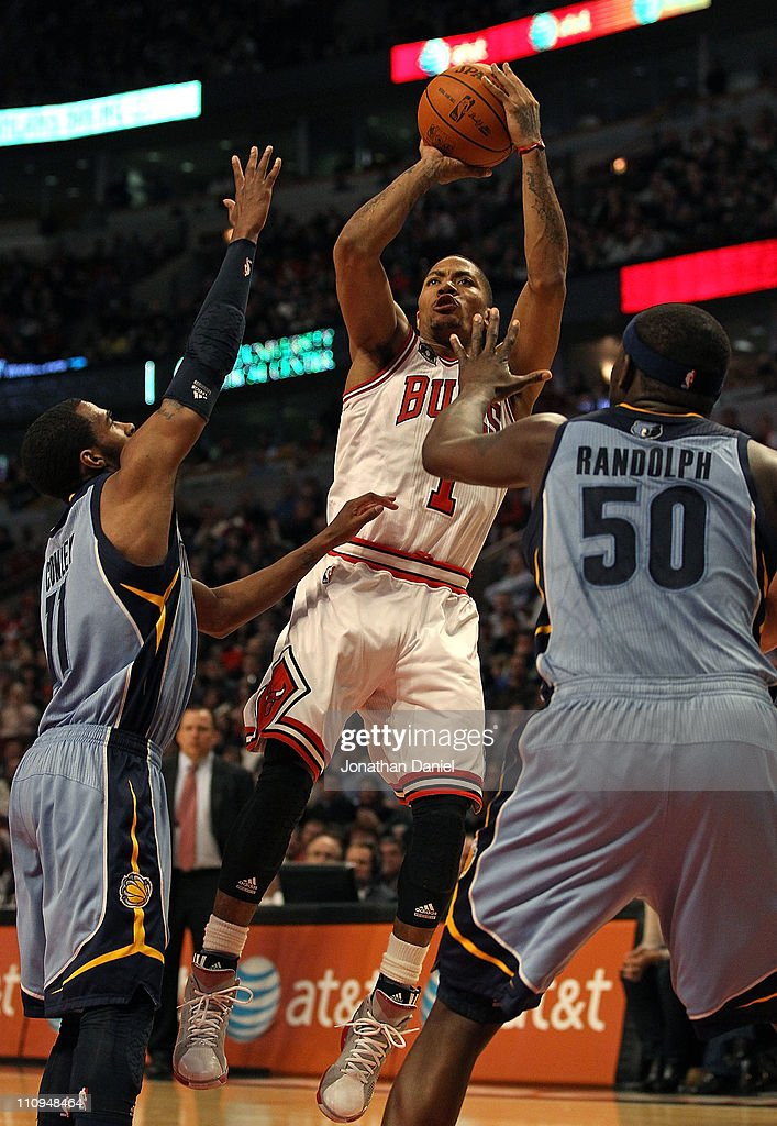 Derrick Rose #1 of the Chicago Bulls puts up a shot between Mike Conley #11 and Zach Randolph #50 of the Memphis Grizzlies at the United Center on March 25, 2011 in Chicago, Illinois. The Bulls defeated the Grizzlies 99-96.