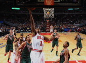 Derrick Rose of the Chicago Bulls puts up a shot over Carlos Delfino and Shaun Livingston of the Milwaukee Bucks at the United Center on February 22...