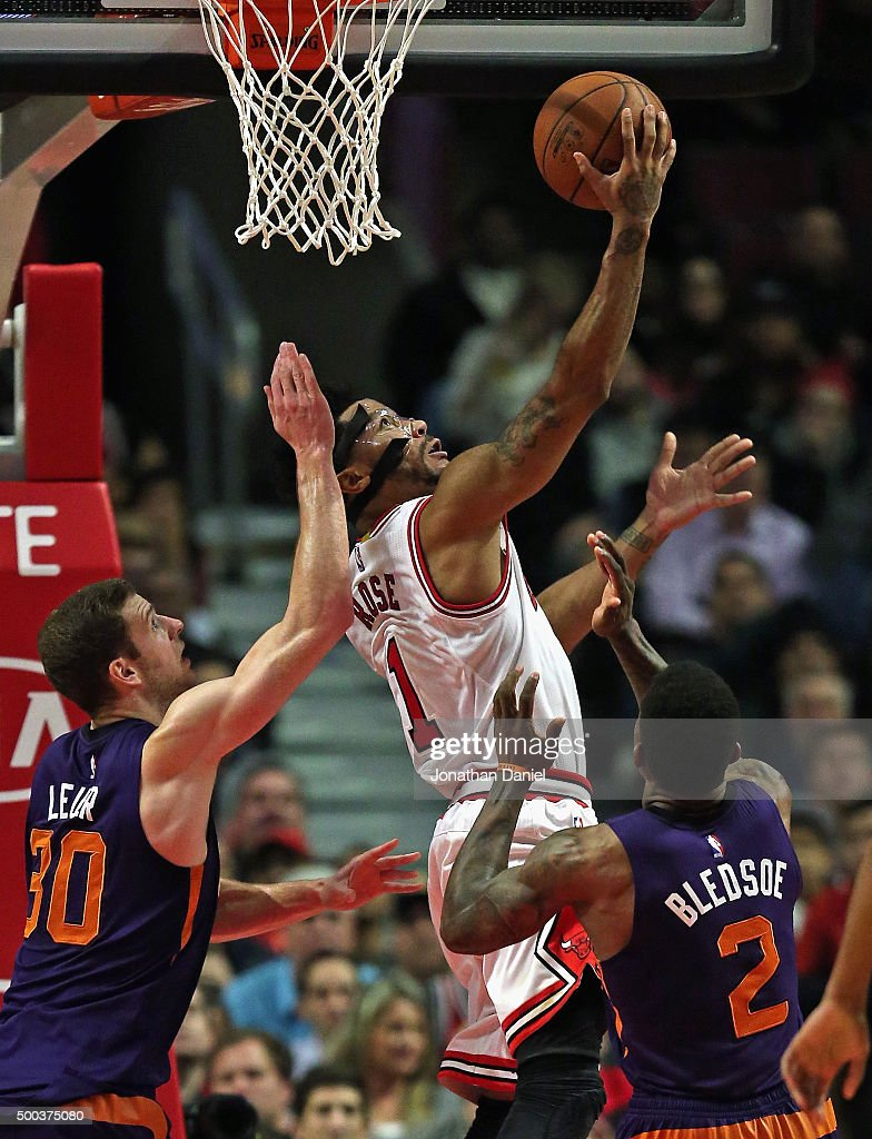 Derrick Rose #1 of the Chicago Bulls puts up a shot over Jon Leuer #30 and Eric Bledsoe #2 of the Phoenix Suns at the United Center on December 7, 2015 in Chicago, Illinois. The Suns defeated the Bulls 103-101.