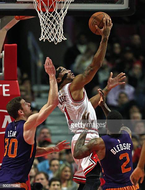 Derrick Rose of the Chicago Bulls puts up a shot over Jon Leuer and Eric Bledsoe of the Phoenix Suns at the United Center on December 7 2015 in...