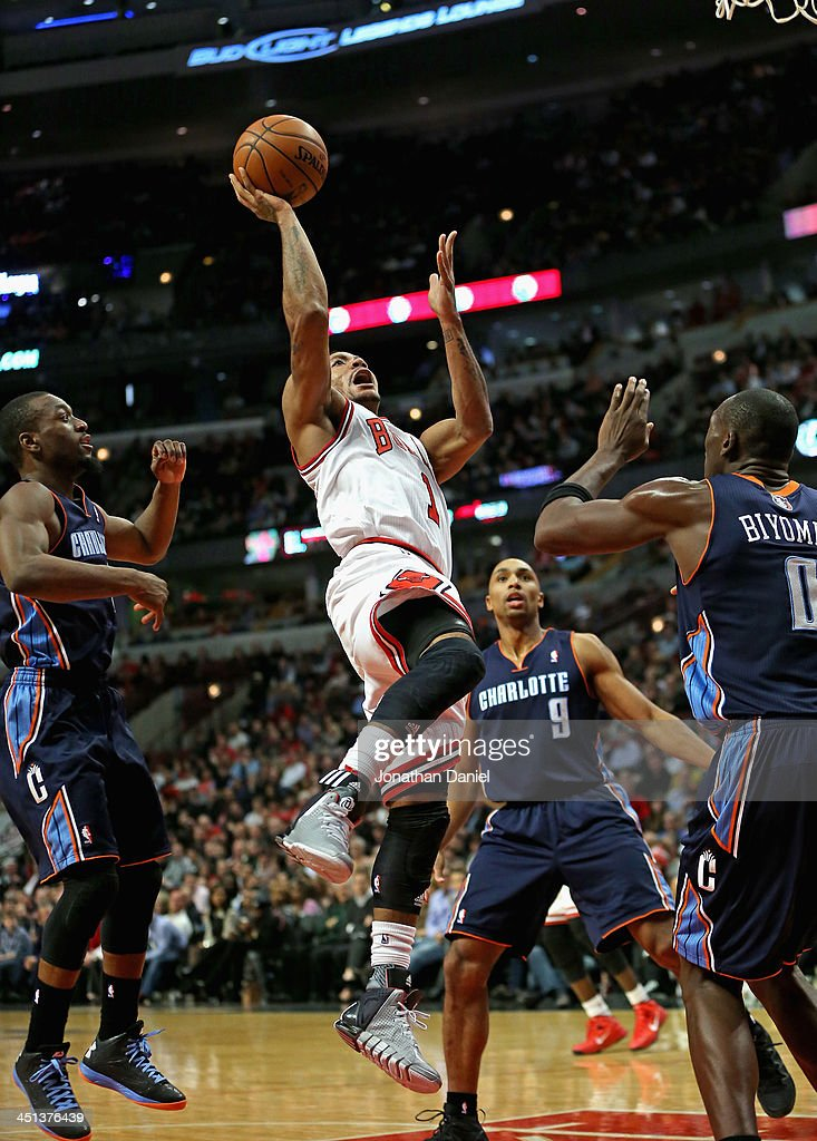Derrick Rose of the Chicago Bulls shoots over Bismack Biyombo of the Charlotte Bobcats at the United Center on November 18 2013 in Chicago Illinois...