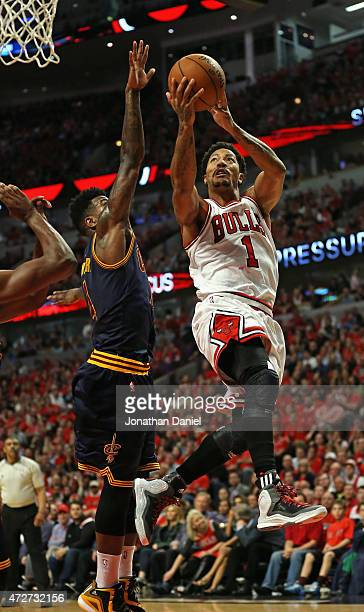 Derrick Rose of the Chicago Bulls shoots over Iman Shumpert of the Cleveland Cavaliers on his way to a gamehigh 30 points in Game Three of the...