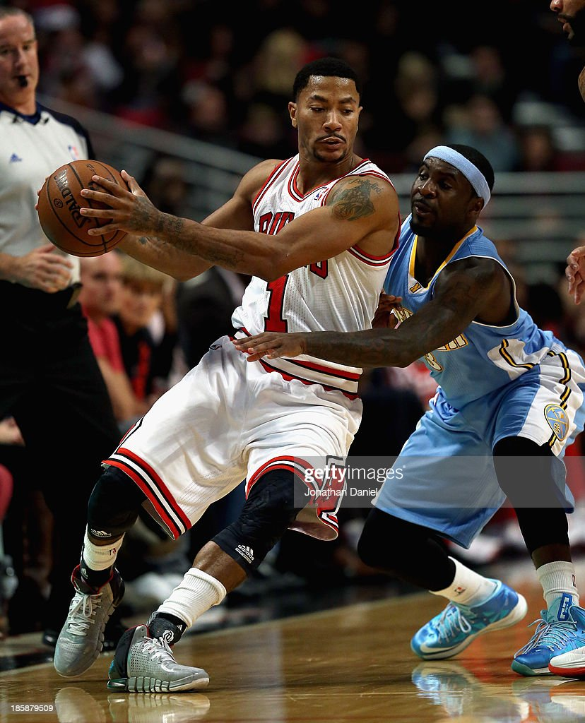 Derrick Rose of the Chicago Bulls works against Ty Lawson of the Denver Nuggets during a preseason game at the United Center on October 25 2013 in...