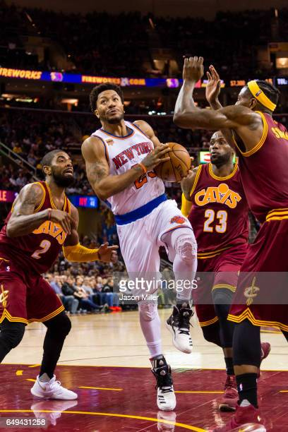 Derrick Rose of the New York Knicks looks to shoot while under pressure from Kyrie Irving LeBron James and Iman Shumpert of the Cleveland Cavaliers...