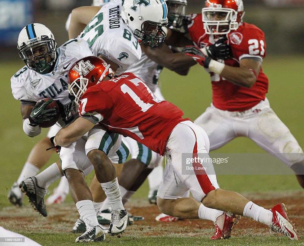 Derrick Strozier #13 of the Tulane Green Wave is hit by Chris Cermin #17 of the Houston Cougars at Robertson Stadium on November 24, 2012 in Houston, Texas. Houston defeats Tulane 40-17.