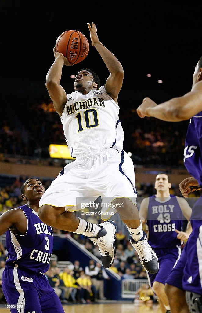 Derrick Walton Jr. #10 of the Michigan Wolverines gets to the basket past Justin Burrell #3 of the Holy Cross Crusaders during the first half at Crisler Center on December 28, 2013 in Ann Arbor, Michigan.