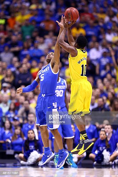 Derrick Walton Jr #10 of the Michigan Wolverines shoots the ball over Andrew Harrison of the Kentucky Wildcats in the first half during the midwest...