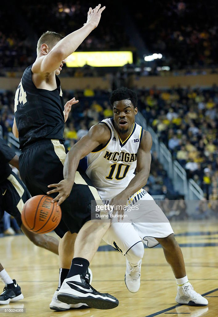 Derrick Walton #10 of the Michigan Wolverines passes around Isaac Haas #44 of the Purdue Boilermakers during the first half at Crisler Arena on February 13, 2016 in Ann Arbor, Michigan.