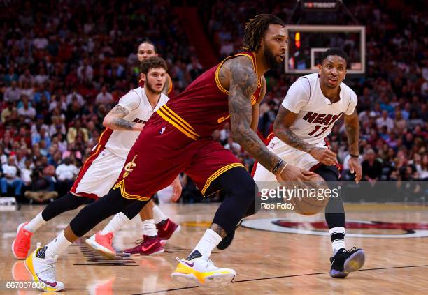 Derrick Williams of the Cleveland Cavaliers drives past Tyler Johnson and Rodney McGruder of the Miami Heat during the first half of the game at the...