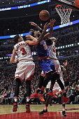 Derrick Williams of the New York Knicks looses control of the ball as he tries to shoot between Doug McDermott and Taj Gibson of the Chicago Bulls at...