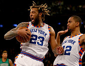 Derrick Williams of the New York Knicks reacts after he grabs the rebound in the final minute of the game as teammate Lance Thomas looks on against...