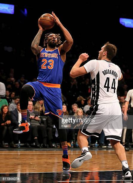 Derrick Williams of the New York Knicks takes a shot as Bojan Bogdanovic of the Brooklyn Nets defends at Barclays Center on February 19 2016 in the...