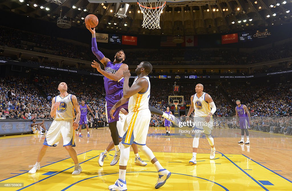 Derrick Williams #13 of the Sacramento Kings shoots a layup against <a gi-track='captionPersonalityLinkClicked' href=/galleries/search?phrase=Draymond+Green&family=editorial&specificpeople=5628054 ng-click='$event.stopPropagation()'>Draymond Green</a> #23 of the Golden State Warriors on April 4, 2014 at Oracle Arena in Oakland, California.