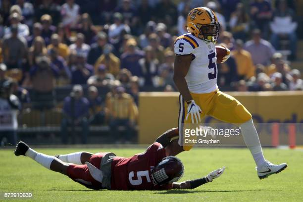 Derrius Guice of the LSU Tigers avoids a tackle by Henre' Toliver of the Arkansas Razorbacks at Tiger Stadium on November 11 2017 in Baton Rouge...