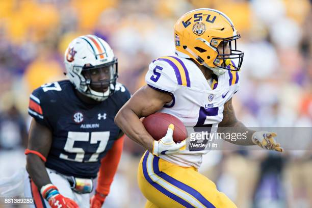Derrius Guice of the LSU Tigers runs the ball and is chased by Deshaun Davis of the Auburn Tigers at Tiger Stadium on October 14 2017 in Baton Rouge...