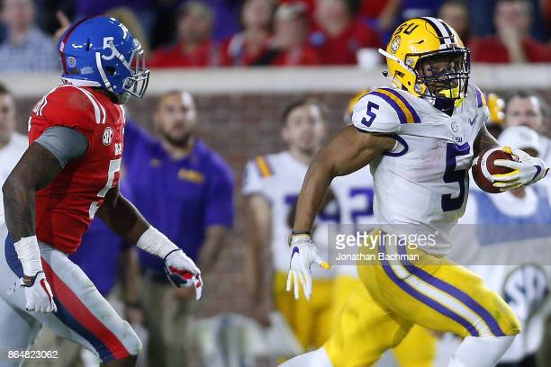 Derrius Guice of the LSU Tigers runs with the ball as Ken Webster of the Mississippi Rebels defends during the second half of a game at...