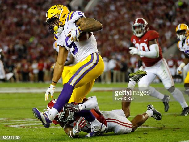 Derrius Guice of the LSU Tigers tries to break a tackle by Anthony Averett of the Alabama Crimson Tide at BryantDenny Stadium on November 4 2017 in...