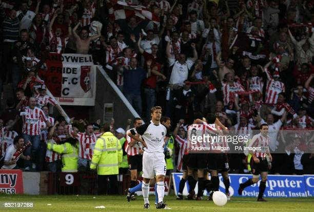 Derry City's players celebrate their third goal as Gretna's Chris Innes shows his dejection during the UEFA Cup second qualifying round first leg...