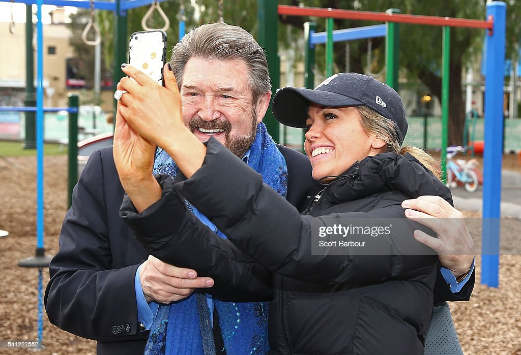 Derry Hinch, a candidate for the senate representing Victoria as the head of 'Derryn Hinch's Justice Party' poses for a selfie with a supporter as he arrives to vote in the national election at a polling station at Albert Park Primary School on July 2, 2016 in Melbourne, Australia. Voters head to the polls today to elect the 45th parliament of Australia.