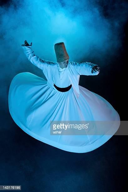 Dervish spinning in white from above on black background