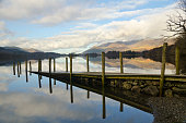 An old jetty stretches out into the calm and tranquil waters of Derwentwater in the English Lake District Cumbria.