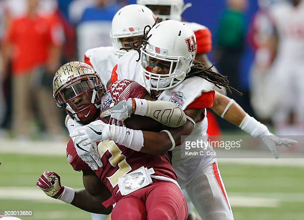 Derwin James of the Florida State Seminoles is tackled by Trevon Stewart of the Houston Cougars in the second quarter during the ChickfilA Peach Bowl...