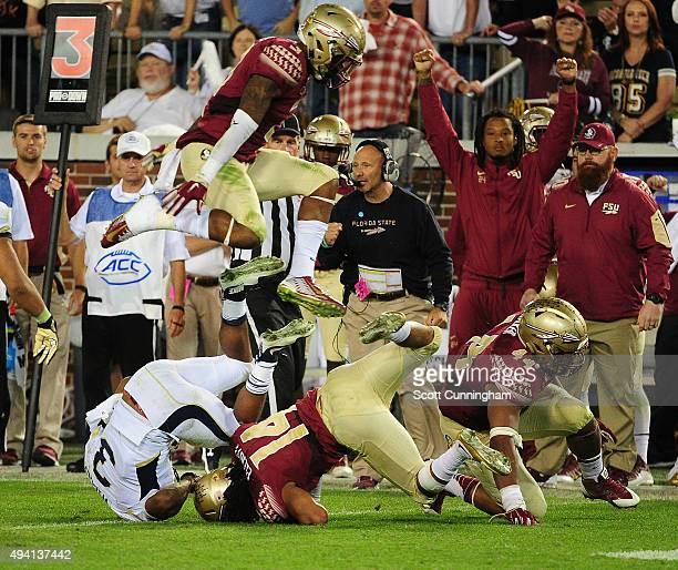 Derwin James of the Florida State Seminoles leaps over the pile after Isiah Willis of the Georgia Tech Yellow Jackets is tackled by the Seminoles...