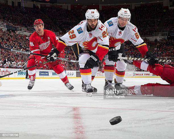 Deryk Engelland and Brett Kulak of the Calgary Flames skate after a loose puck followed by Luke Glendening of the Detroit Red Wings during an NHL...