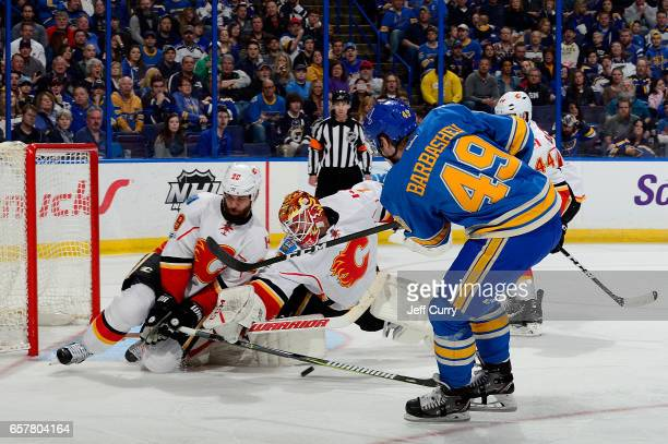 Deryk Engelland and Brian Elliott of the Calgary Flames stop a shot by Ivan Barbashev of the St Louis Blues on March 25 2017 at Scottrade Center in...