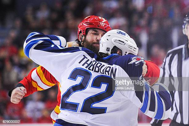 Deryk Engelland of the Calgary Flames fights Chris Thorburn of the Winnipeg Jets during an NHL game at Scotiabank Saddledome on December 10 2016 in...