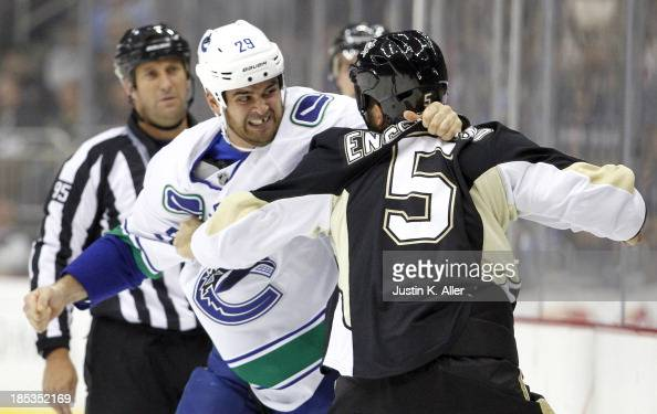 Deryk Engelland of the Pittsburgh Penguins and Tom Sestito of the Vancouver Canucks mix it up during the game at Consol Energy Center on October 19...