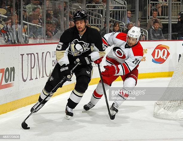 Deryk Engelland of the Pittsburgh Penguins moves the puck in front of JohnMichael Liles of the Carolina Hurricanes on April 1 2014 at Consol Energy...
