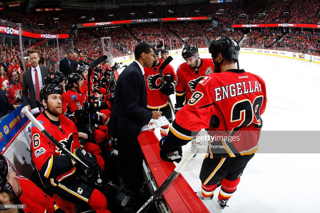Deryk Engelland #29, Troy Brouwer #36, and teammates of the Calgary Flames skates get instructions during an NHL game against the Pittsburgh Penguins on March 13, 2017 at the Scotiabank Saddledome in Calgary, Alberta, Canada.