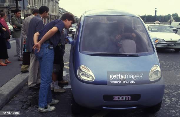 Des curieux regardent la microvoiture electrique Renault Matra Zoom sur la place de la Concorde le 27 aout 1992 a Paris France