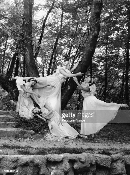 Des danseuses en robes blanches prennent la pause autour d'un arbre à côté d'un escalier en pierre
