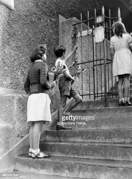 Des enfants avec des fleurs rendent hommage à l'artiste Francisque Poulbot devant sa maison à Montmartre après son décès en septembre 1946 à Paris...
