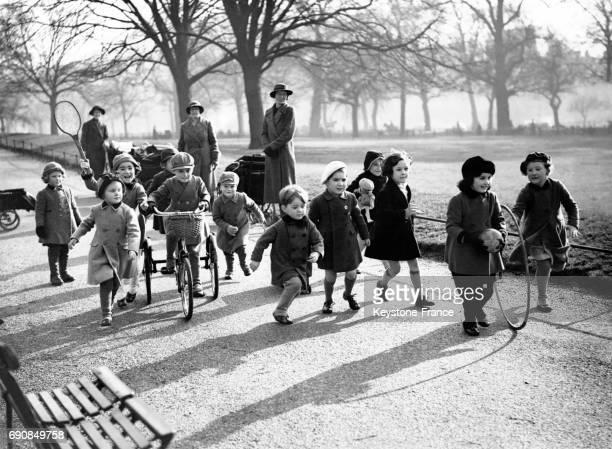 Des enfants courent et font du vélo dans les allées de Hyde Park ensoleillées à Londres RoyaumeUni le 4 février 1938