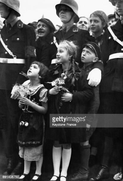 Des enfants devant des soldats nazis lèvent le visage vers les fenêtres de la Chancellerie du Reich dans l'espoir d'apercevoir Adolf Hitler afin de...