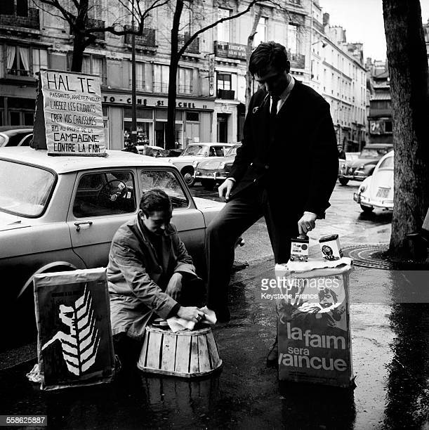 Des etudiants cirent des chaussures a des passants sur la place SaintMichel pour participer a la campagne contre la faim le 23 mars 1965 a Paris...