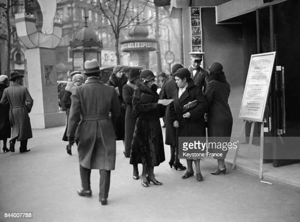 Des femmes devant l'entrée d'un cinéma lisent le programme des films à l'affiche à Paris France en décembre 1932