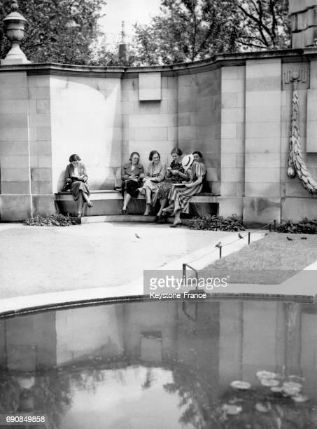 Des femmes ont trouvé une alcove ombragée pour déjeuner à Embankment Park à Londres RoyaumeUni le 27 mai 1937
