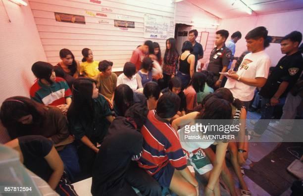Des filles sont controlees par des policiers lors d'une descente de police dans un bordel en juin 1994 en Thailande