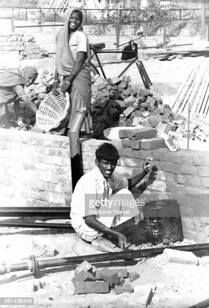 Des hommes et femmes pauvres travaillent comme petite main d'oeuvre sur un chantier de constrution à New Delhi Inde