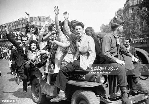Des jeunes femmes et des jeunes hommes avec un GI sur une Jeep de l'armée américaine bras en l'air dans la rue à Paris France le 8 mai 1945