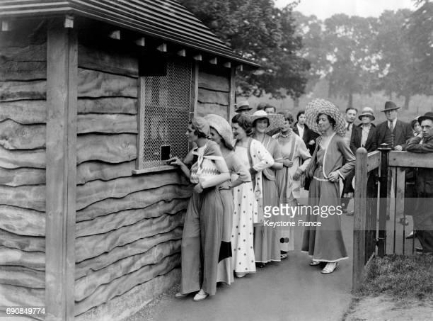 Des jeunes femmes font la queue pour acheter leur ticket d'entrée à la piscine en plein air à Hyde Park Londres RoyaumeUni circa 1930