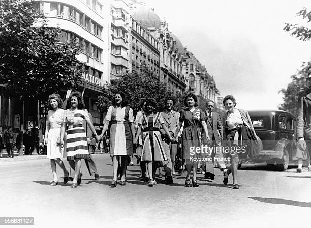Des jeunes filles vêtues des drapeaux des Forces alliées défilant dans la rue pour fêter l'armistice le 8 mai 1945 à Paris France